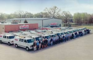 Photo from 1974 of Hanna Inc and its large staff standing in front of 2 long rows of hvac trucks and vans at the Wichita location