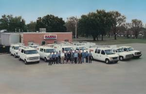 Photo from the 1970s of Hanna Inc and its large staff standing in front of 2 long rows of hvac trucks and vans at the Wichita location