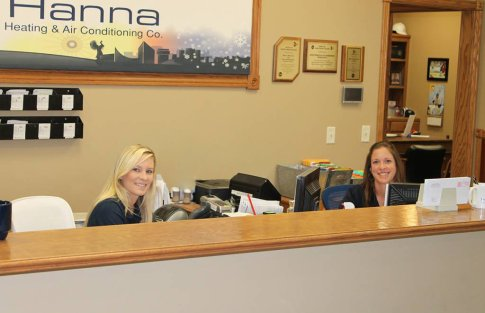 Two Hanna Heating and Air team members smiling at our front desk, helping to serve Wichita, Andover and Newton