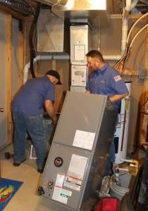 Hanna heating technicians installing new high efficiency furnace in Wichita home.