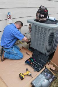 Hanna AC tech working on outside air conditioning condenser unit