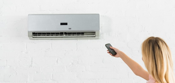 Woman changing setting on a mini split system for cooling a home office